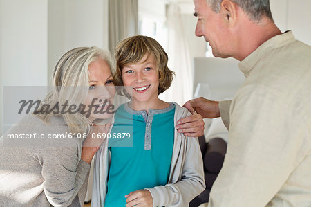 Grandparents hugging their grandson at home Stock Photo - Premium Royalty-Free, Image code: 6108-06906879