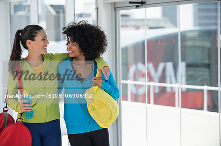 Two happy female friends carrying gym bags Stock Photo - Premium Royalty-Free, Image code: 6108-06906912