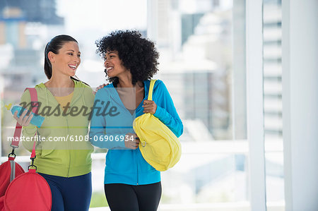 Two happy female friends carrying gym bags Stock Photo - Premium Royalty-Free, Image code: 6108-06906934