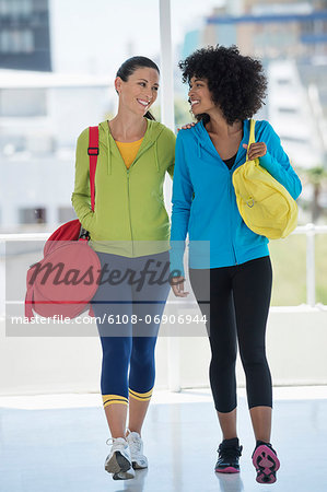 Two happy female friends carrying gym bags Stock Photo - Premium Royalty-Free, Image code: 6108-06906944