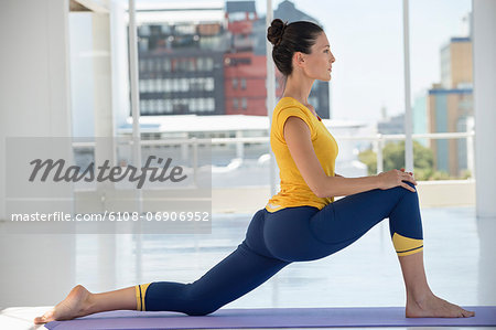 Woman exercising on exercise mat in a gym Stock Photo - Premium Royalty-Free, Image code: 6108-06906952