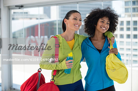 Two happy female friends carrying gym bags Stock Photo - Premium Royalty-Free, Image code: 6108-06906992