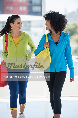 Two happy female friends carrying gym bags Stock Photo - Premium Royalty-Free, Image code: 6108-06907008