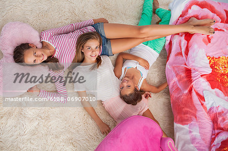 Three girls lying on a carpet at a slumber party Stock Photo - Premium Royalty-Free, Image code: 6108-06907010
