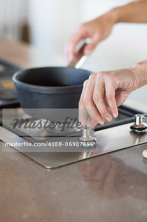 Woman cooking in the kitchen Stock Photo - Premium Royalty-Free, Image code: 6108-06907095