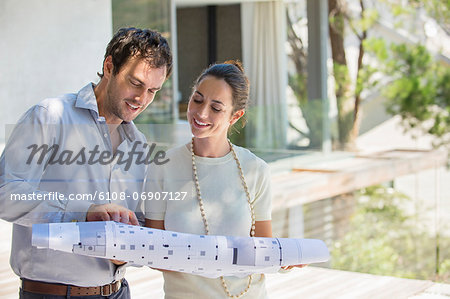 Couple looking at blueprint and smiling Stock Photo - Premium Royalty-Free, Image code: 6108-06907127