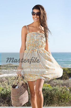 Beautiful woman carrying a bag on the beach Stock Photo - Premium Royalty-Free, Image code: 6108-06907228