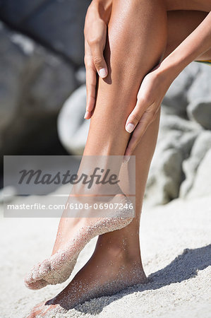 Woman applying suntan lotion on her leg on the beach Stock Photo - Premium Royalty-Free, Image code: 6108-06907246