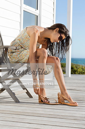 Beautiful woman putting on sandal at beach resort Stock Photo - Premium Royalty-Free, Image code: 6108-06907261