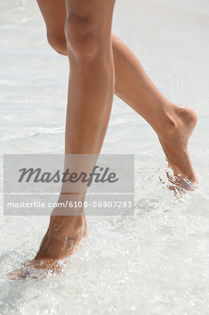 Woman walking in water on the beach Stock Photo - Premium Royalty-Free, Image code: 6108-06907283