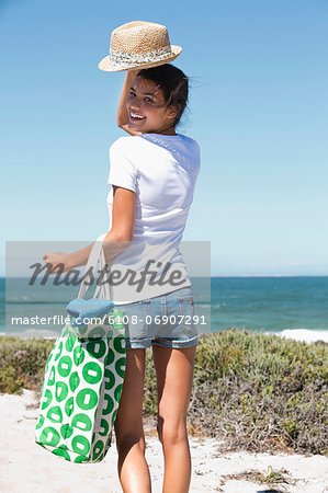 Happy woman carrying a bag on the beach Stock Photo - Premium Royalty-Free, Image code: 6108-06907291