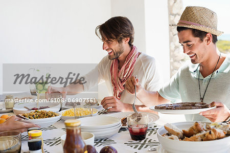 Friends eating lunch at dining table Stock Photo - Premium Royalty-Free, Image code: 6108-06907361