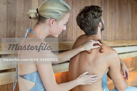 Woman massaging on her friend's back with a massager in a sauna Stock Photo - Premium Royalty-Free, Image code: 6108-06907503