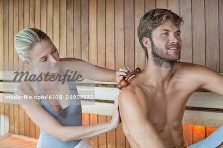 Woman massaging on her friend's back with a massager in a sauna Stock Photo - Premium Royalty-Free, Image code: 6108-06907532