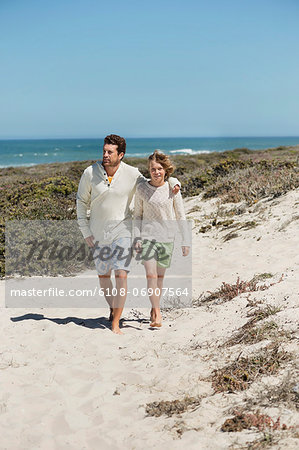 Man walking with his son on the beach Stock Photo - Premium Royalty-Free, Image code: 6108-06907564