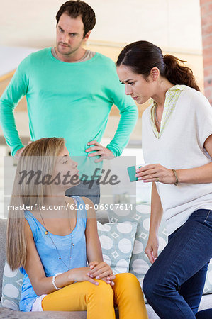 Parents scolding their daughter at home Stock Photo - Premium Royalty-Free, Image code: 6108-06907614