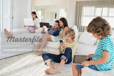 Family using electronics gadget Stock Photo - Premium Royalty-Free, Image code: 6108-06907615