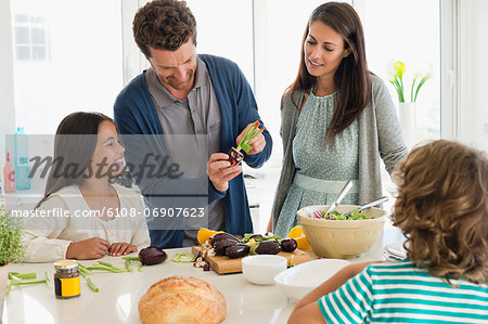 Family preparing food in the kitchen Stock Photo - Premium Royalty-Free, Image code: 6108-06907623