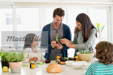 Family preparing food in the kitchen Stock Photo - Premium Royalty-Free, Image code: 6108-06907634