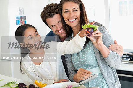 Couple with their daughter enjoying in the kitchen Stock Photo - Premium Royalty-Free, Image code: 6108-06907638