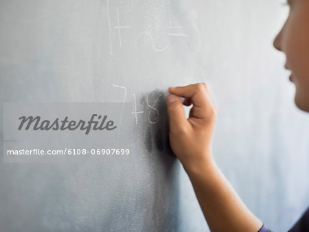 Close-up of a boy writing on a blackboard in a classroom Stock Photo - Premium Royalty-Free, Image code: 6108-06907699