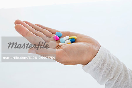 Close-up of a woman's hand holding medicines Stock Photo - Premium Royalty-Free, Image code: 6108-06907759