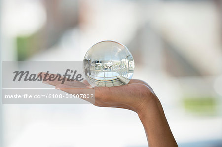 Close-up of a person's hand holding a crystal ball Stock Photo - Premium Royalty-Free, Image code: 6108-06907802