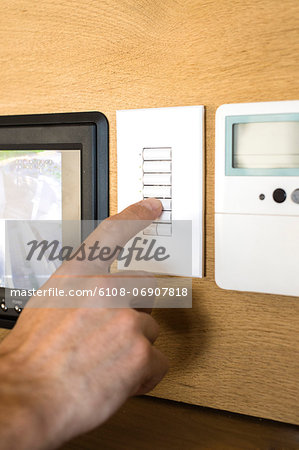 Person pressing switch of a security camera control panel Stock Photo - Premium Royalty-Free, Image code: 6108-06907818