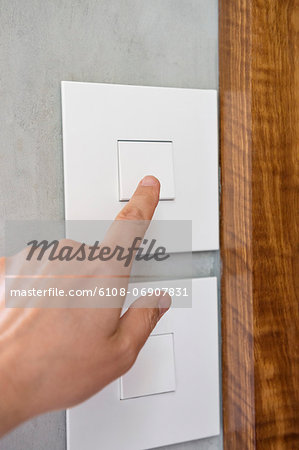 Close-up of a person's hand pressing a light switch Stock Photo - Premium Royalty-Free, Image code: 6108-06907831