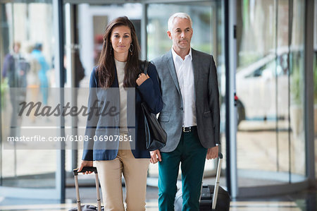 Business couple pulling suitcases in a hotel lobby Stock Photo - Premium Royalty-Free, Image code: 6108-06907851