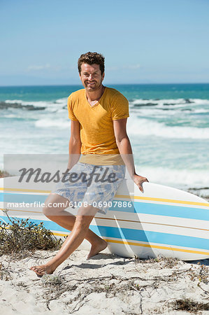 Man sitting on a surfboard on the beach Stock Photo - Premium Royalty-Free, Image code: 6108-06907886