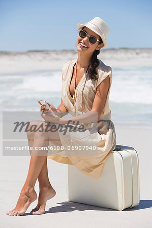 Beautiful woman sitting on a suitcase and holding a cell phone on the beach Stock Photo - Premium Royalty-Free, Image code: 6108-06907940