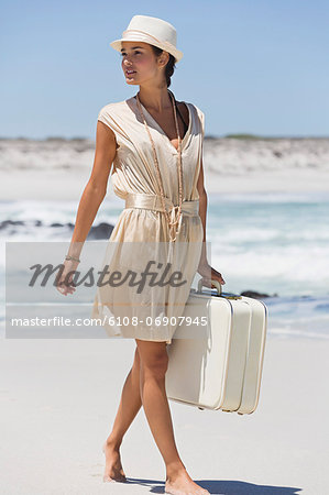 Beautiful woman carrying a suitcase on the beach Stock Photo - Premium Royalty-Free, Image code: 6108-06907945