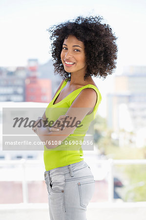 Woman standing with her arms crossed and smiling Stock Photo - Premium Royalty-Free, Image code: 6108-06908056