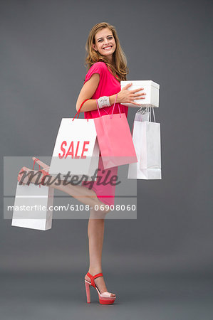 Portrait of a woman posing with shopping bags and smiling Stock Photo - Premium Royalty-Free, Image code: 6108-06908060