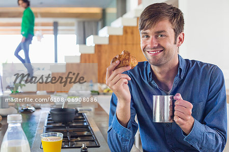 Man having breakfast at a kitchen counter with his wife in the background Stock Photo - Premium Royalty-Free, Image code: 6108-06908086