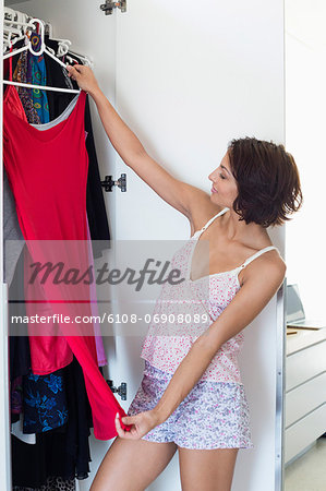 Woman choosing clothes from wardrobe Stock Photo - Premium Royalty-Free, Image code: 6108-06908089