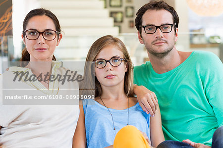 Portrait of a family sitting on a couch and wearing eyeglasses Stock Photo - Premium Royalty-Free, Image code: 6108-06908099