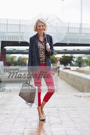 Smiling woman under an umbrella carrying shopping bags Stock Photo - Premium Royalty-Free, Image code: 6108-06908125