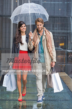 Couple with shopping bags sheltering under umbrella in rain Stock Photo - Premium Royalty-Free, Image code: 6108-06908128