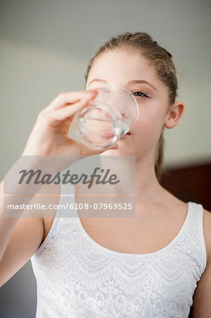Girl drinking a glass of water Stock Photo - Premium Royalty-Free, Image code: 6108-07969525