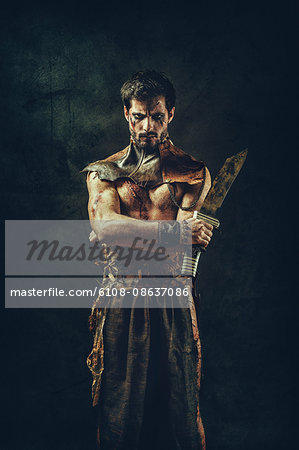Portrait of a tribal warrior standing arms crossed Stock Photo - Premium Royalty-Free, Image code: 6108-08637086
