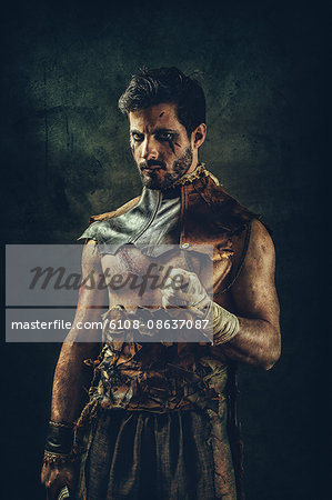 Portrait of a tribal warrior standing clenched fist Stock Photo - Premium Royalty-Free, Image code: 6108-08637087