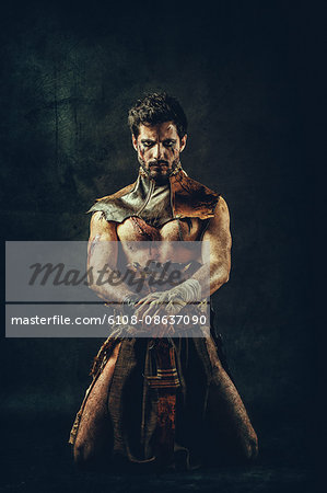 Tribal warrior kneeling Stock Photo - Premium Royalty-Free, Image code: 6108-08637090