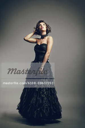 Young woman in evening dress looking up, hands behind head Stock Photo - Premium Royalty-Free, Image code: 6108-08637201