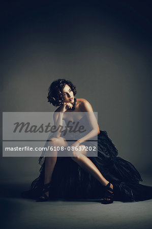 Young woman sitting in evening dress, look on the side Stock Photo - Premium Royalty-Free, Image code: 6108-08637202