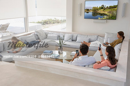 Family in living room busy in different activities Stock Photo - Premium Royalty-Free, Image code: 6108-08662941