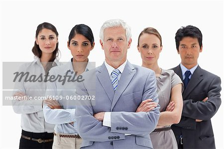 Close-up of a multicultural business team behind their boss against white background Stock Photo - Premium Royalty-Free, Image code: 6109-06002702