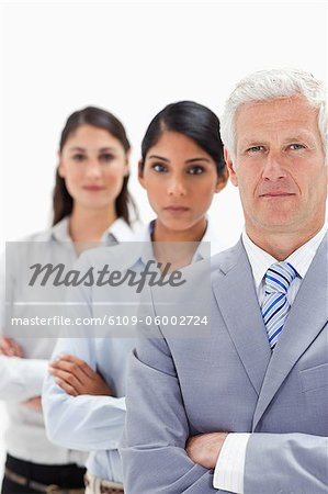 Close-up of a business man with two women behind him against white background Stock Photo - Premium Royalty-Free, Image code: 6109-06002724
