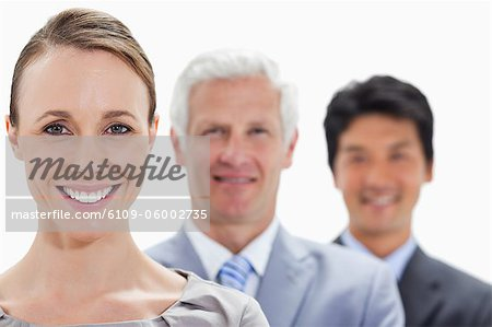 Close-up of smiling business people in a single line with focus on the woman against white background Stock Photo - Premium Royalty-Free, Image code: 6109-06002735